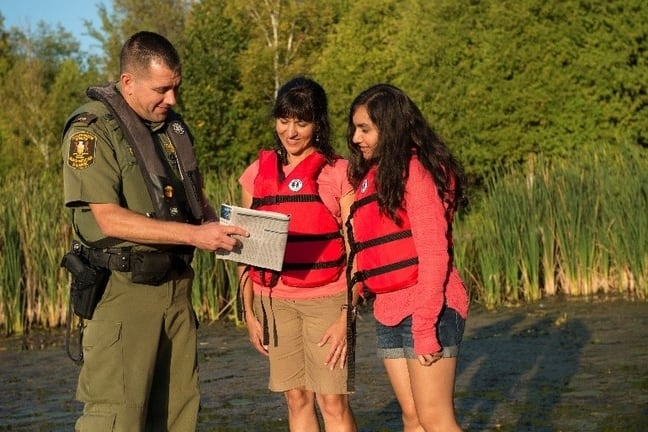 Image of conservation officer showing Fishing Regulations Summary to two women.