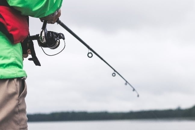 Image of person reeling in fishing rod.