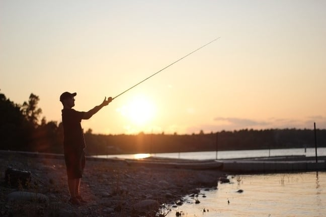 Image of man casting from shore during sunset.