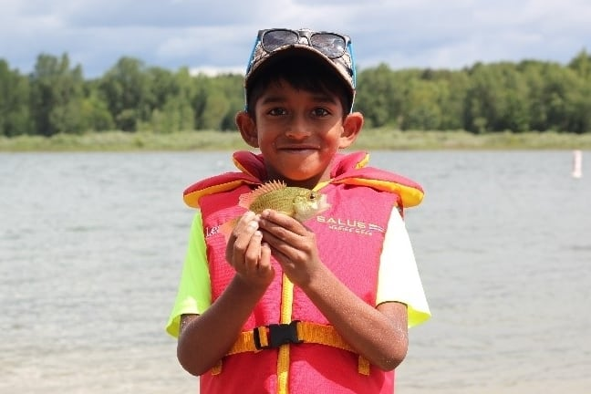 Image of boy with life jacket smiling while holding a small fish.