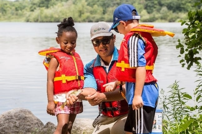 Image of a Learn to Fish instructor showing two children how to hold a small fish.